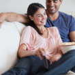 Stock Photo: Delighted couple watching TV while eating popcorn