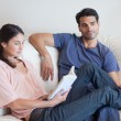 Royalty-Free Stock Photo: Woman reading a book while her boyfriend is watching television