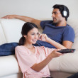 Woman watching TV while her boyfriend is listening to music — Stock Photo