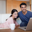 Young couple using a laptop while having a tea — Stock Photo #11206574