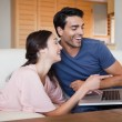 Laughing young couple using a laptop — Stock Photo #11206580