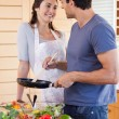 Portrait of a beautiful couple cooking with a pan — Stock Photo