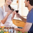 Portrait of a couple having a glass of red wine while cooking — Stock Photo