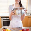 Portrait of a woman showing a sauce pan — Stock Photo