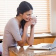 Lovely woman using a laptop while drinking a cup of a coffee — Stock Photo