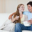 Charming couple watching television while eating popcorn — Stock Photo