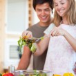 Portrait of a young couple making a salad — Stock Photo