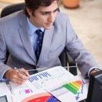 Businessman analyzing statistics at his desk — Stock Photo