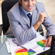 Stock Photo: Smiling businessmworking on statistics