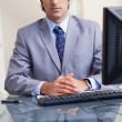 Businessman sitting behind his computer — Stock Photo