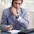 Businessman taking notes while on the phone — Stock Photo