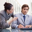 Stockfoto: Businessmtaking notes while getting explanation by colleague