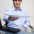 Foto Stock: Smiling businessmhanding over paperwork