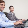 Side view of smiling colleagues working next to each other — Stock Photo