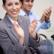 Side view of clapping business team sitting at desk — Stock Photo