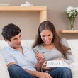 Woman opening present from her boyfriend on the sofa — Stock Photo