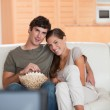 Couple with bowl of popcorn watching a movie on the sofa — Stock Photo