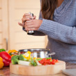 Woman adding pepper to her vegetable stew - Foto Stock