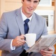 Businessman having coffee and reading news in the kitchen — Stock Photo