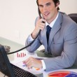 Smiling businessman on the phone working on statistics — Stock Photo #11208173