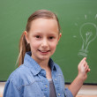 Smiling schoolgirl pointing at a bulb — Stock Photo