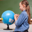 Stock Photo: Schoolgirl looking at a globe