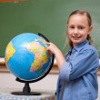 Smiling schoolgirl looking at a globe — Stock Photo