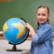 Stock Photo: Smiling schoolgirl looking at a globe