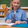 Foto Stock: Portrait of a happy schoolgirl writing