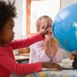 Happy schoolgirls looking at a globe — Stock Photo