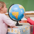 Smiling schoolgirls looking at a globe — Stock Photo #11208548