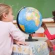 Cute schoolgirls looking at a globe — Stock Photo