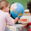Stock Photo: Little schoolgirls looking at globe