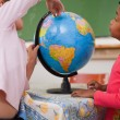 Stock Photo: Cute little schoolgirls looking at globe