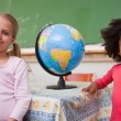 Schoolgirls posing with a globe — Stock Photo