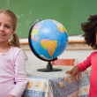 Stock Photo: Cute schoolgirls posing with globe