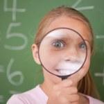 šťastný školačka při pohledu skrz zvětšovací sklo — Stock fotografie