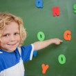 Schoolboy pointing at a letter — Stock Photo