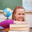 Portrait of schoolgirl posing with a stack of books — Stock Photo