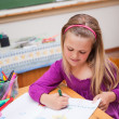 Portrait of a cute schoolgirl drawing — Stockfoto