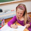 Portrait of a cute schoolgirl drawing - Photo