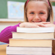 Portrait of a smiling schoolgirl posing with a stack of books — Stock Photo