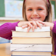 Portrait of a happy schoolgirl posing with a stack of books — Stock Photo