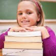 Happy schoolgirl posing with a stack of books — Stock Photo #11208725