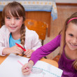 Cute schoolgirls drawing in a coloring book — Stock Photo