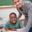 portrait of a teacher explaining something to a smiling schoolbo — Stock Photo