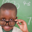 Smiling schoolboy looking over his glasses - Stock Photo