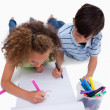 Stock Photo: Portrait of children drawing while lying on the floor