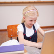 Portrait of a little girl using a laptop — Stock Photo