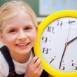 Schoolgirl showing a clock — Stock Photo